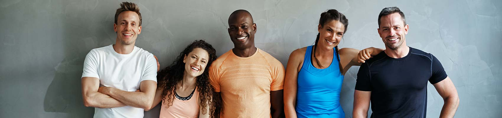 Smiling group of friends in sportswear laughing while standing arm in arm together in a gym.