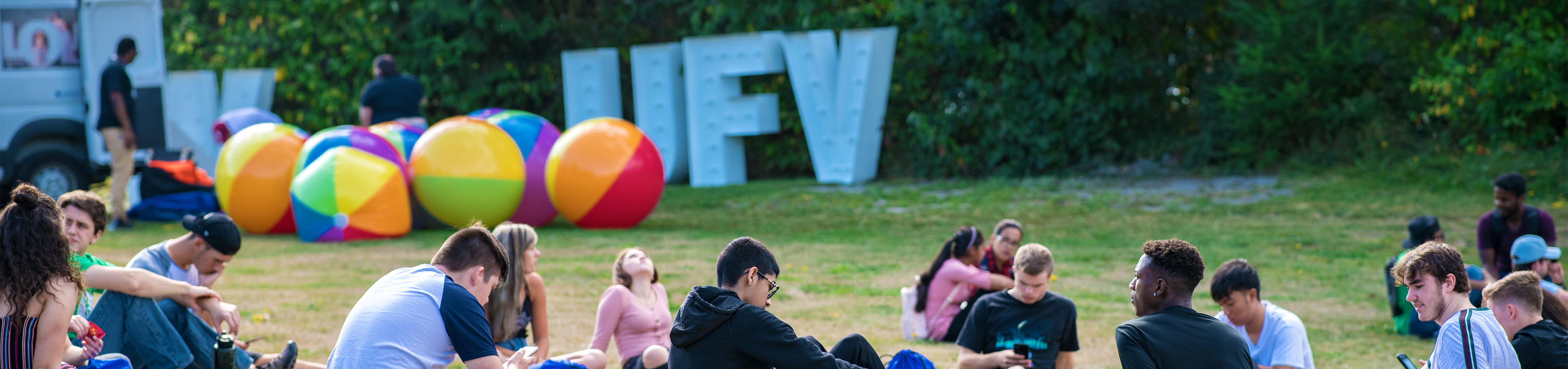 Group of students sitting on the grass on campus in front of colorful balloons and the UFV letters